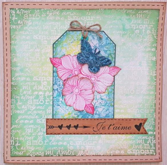 Papier basi'like blanc pour le fond, le tag et les fleurs (BL01) papier basi'like chocolat lait pour la carte (BL03) Tampon de fond Love (WD-0005) Poudre à embosser blanche (PDR-0001)  Encres spray mer turquoise (SPR-0006) et Vert bambou (SPR-0004) papillon blanc (0001)et poudre à embosser bleu pailletée (PDR-0014) Encreur mer turquoise (EC-0006), vert bambou (EC-0004) et Vert orchidée (EC-0019) pour le fond et rose guimauve (EC-0001) pour les fleurs Kraft gommé